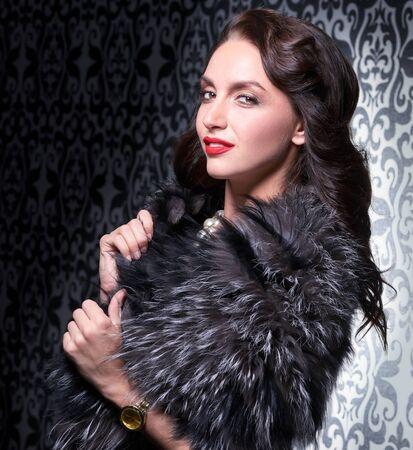 silver fox: Portrait of elegant brunette retro woman wearing silver fox fur over vintage background. Stock Photo