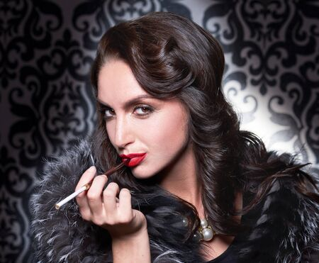 silver fox: Brunette retro with cigarette woman wearing silver fox fur over vintage background. Stock Photo