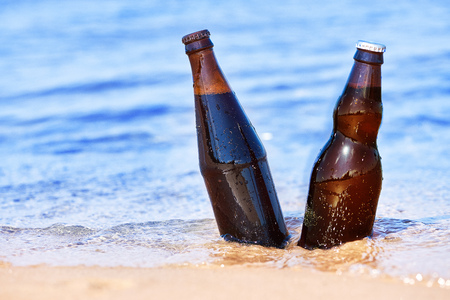 Two bottles of beer in water on the sand.