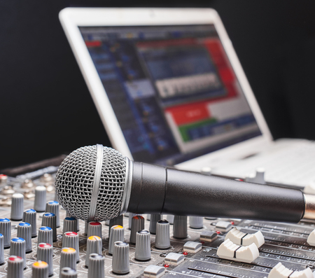 fader: Microphone on sound mixing console. Close up shot with notebook on background