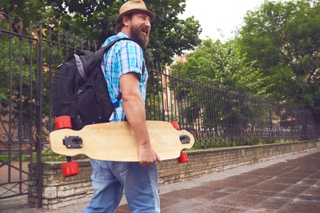 freaky: Freaky bearded man walking with longboard in hand