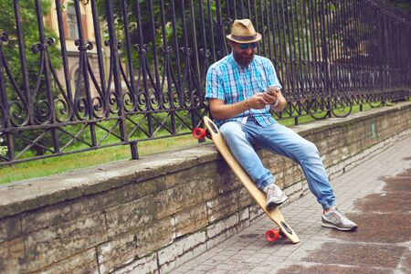 Hipster man sitting at the park with long board. Handsome men in sunglasses and hat posing outdoor. Tonning image Stock Photo