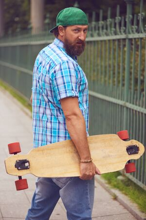 Bearded hipster man posing with longboard and on fashionable green cap Stock Photo