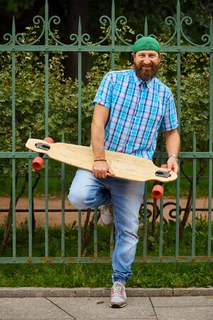 Smiling hipster man posing with longboard and on fashionable green cap