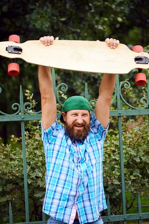 Cheerful hipster man posing with longboard and on fashionable green cap Stock Photo