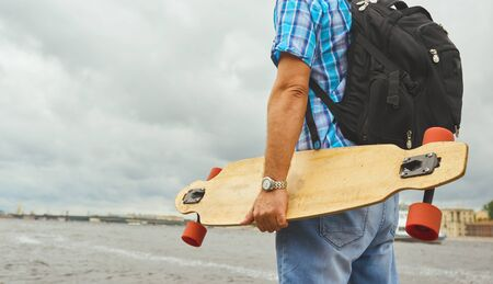 Handsome hipster guy stand with longboard over city river background Stock Photo