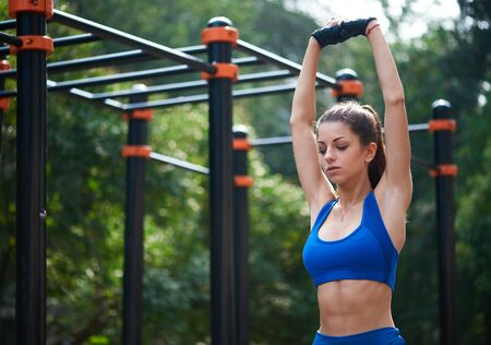 Athletic woman warming up before her morning workout at outdoor workot zone. healthy lifestyle concept Stock Photo