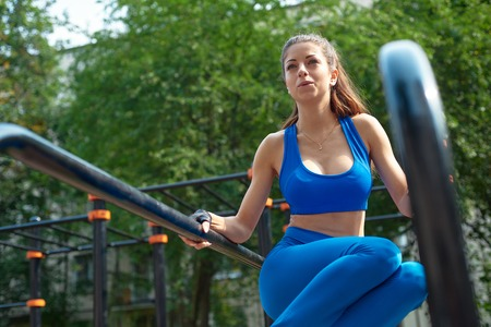 Young woman doing abs exercises outside. outdoor workout on a sunny day. Stock Photo
