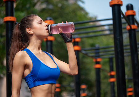 Sportive woman drinking vitamin water at the street gym.