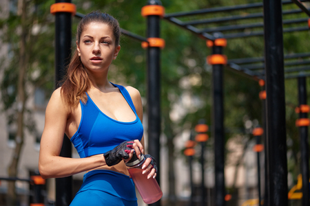 Sportive woman posing with bottle of water at the street gym.