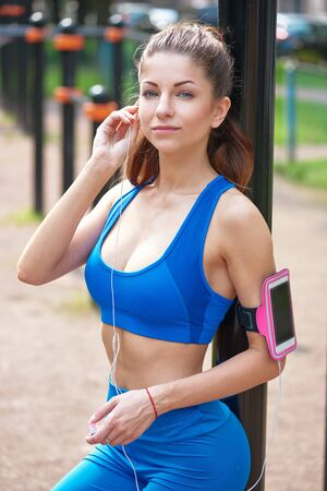 Beautiful woman during fitness on city is listen to the music.