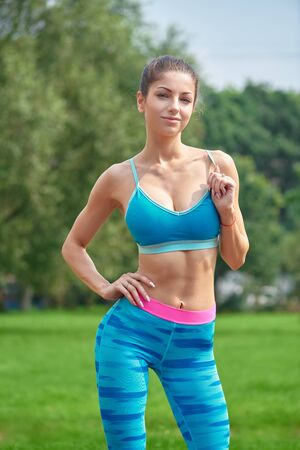 Sporty young woman posing over green grass at park.