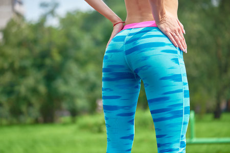 booty shorts: Close up photo of shapely womans buttocks in color shorts at park