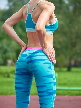 Close up photo of shapely womans buttocks in color shorts at park