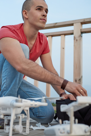 Young man setting drone in park. Close up shot