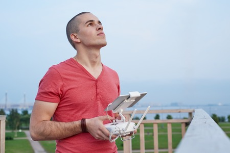 Young man operating a drone remote control console. Imagens