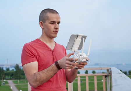 maneuvering: Young man operating a drone remote control console. Stock Photo