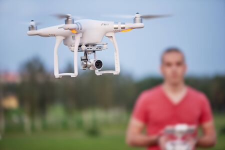 Man controls a quadrocopter. Selective focus on drone, men is blurred. Stock Photo