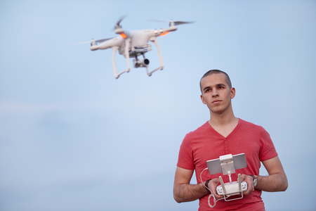 Man controls a quadrocopter. Selective focus on men, drone is blurred.
