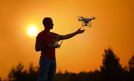 Man controls a quadrocopter. Warm sunset photo.