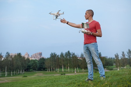 Young man controls a quadrocopter in park. Stock Photo