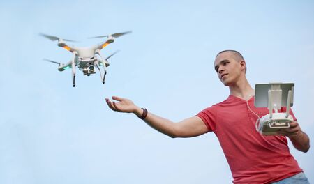 Young man controls a quadrocopter over sky background