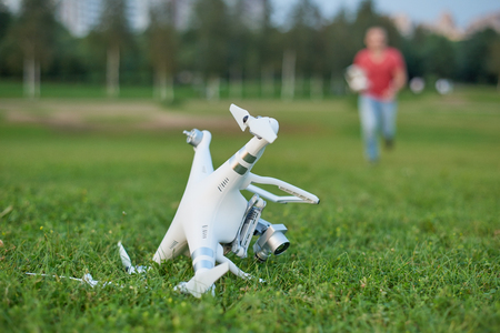 Crashed quadrocopter in park. Propeller damage. Operator running on the background.