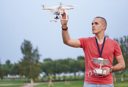 Young man setting a quadrocopter in park.