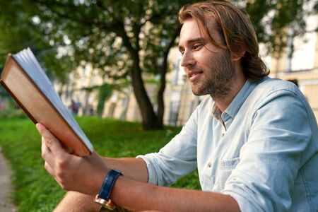 Smiling stubble man holding a book on the grass in the campus. Back to school concept.