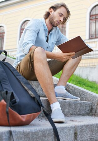 Stubble student read a book sitting on the stairs in university. Foto de archivo