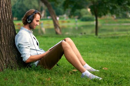 Student with headphones in park of campus read a book. Foto de archivo