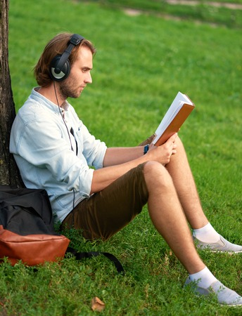 Student with headphones in park of campus read a book. Imagens - 62618300