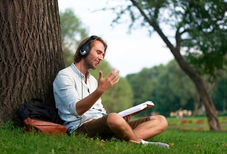 Cheerful student with headphones in park of campus read a book.