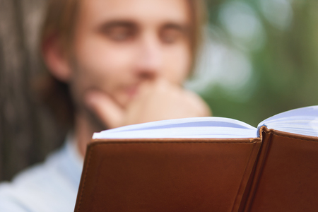 Close up shot. Student in park of campus read a book. Focus on binding