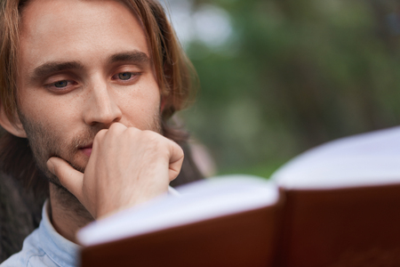Close up shot. Student in park of campus read a book. Focus on man