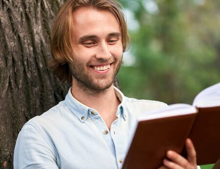 Smiling student in park of campus read a book. Foto de archivo