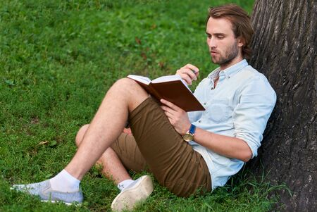 Serious student in park of campus read a book. Foto de archivo