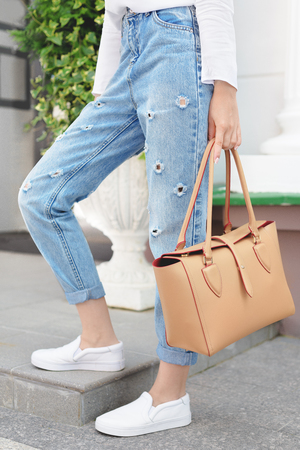 Summer look. White shirt, jeans, brown leather bag and sneakers shoes Imagens