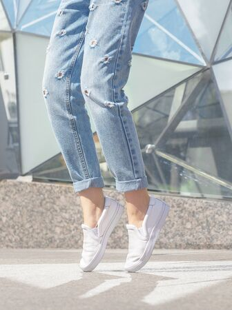 Woman posing. Summer look. White sneakers shoes