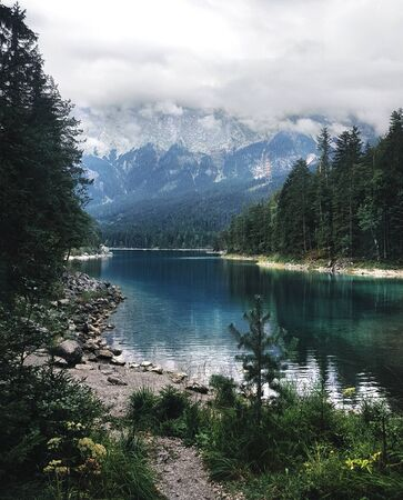 Alpine lake Eibsee with clear blue water, surrounded by trees and mountains covered with fog, vertical shot, Bavaria, Germany