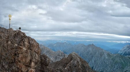 Tourist on the peak of Zugspitze mountain. Hiking and active life concept Imagens - 131985869