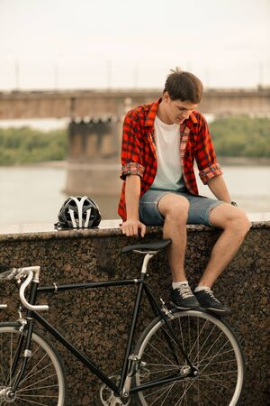 Young man in red shirt sitting on the stairs with a vintage bicycle near him