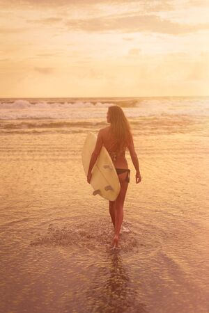 A young woman in bikini stands with her back to the camera and holds a surfboard by the ocean. Warm tinting Imagens