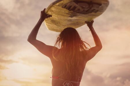 A surfer with long hair standing back to her cell. She holds a white surfboard on her head at sunset. Surfer and ocean