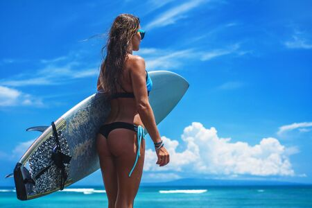 Surfer woman wearing bikinis and glasses with a blue board against the ocean and blue sky with clouds
