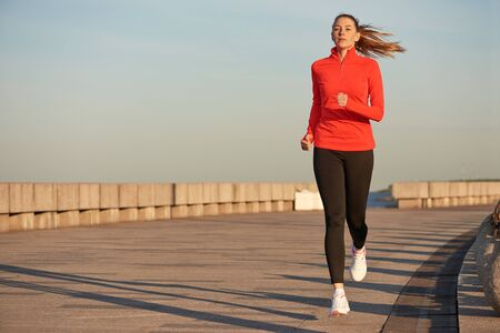 A jogging woman in red running shirt and black leggins on the street at sunrise. Running on concrete quay Imagens