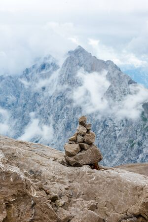 Stones cairn bridging on Zugspitze peak, Alps, Germany. Bavarian Alps on background. Touristic, hiking concept Imagens