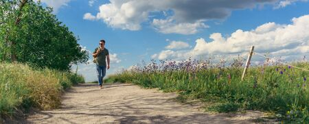 Traveller with backpack and glasses walking down the village gravel path. Panoramic shot. Imagens