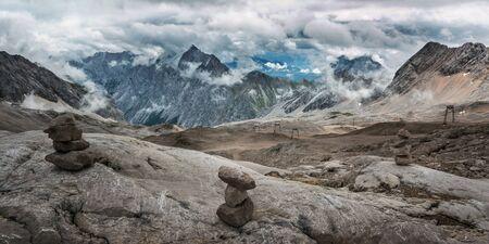 Stones cairn bridging on Zugspitze peak, Alps, Germany Imagens