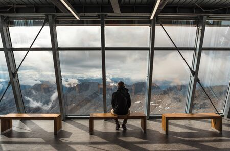 A man sitting on the observation deck on a Zugspitze mountain Imagens